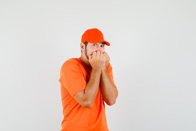 Dostawca w pomarańczowym t-shirt, czapka gryząca pięści emocjonalnie i wyglądająca na przestraszoną, widok z przodu.