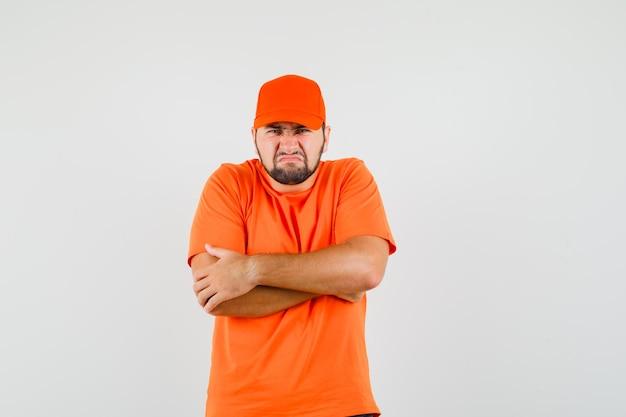 Dostawca w pomarańczowym t-shirt, czapka stojąca z ciasno skrzyżowanymi rękami i patrząc obrażony, widok z przodu.