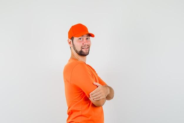Dostawca w pomarańczowym t-shirt, czapka stojąca ze skrzyżowanymi rękami i wyglądająca pewnie.