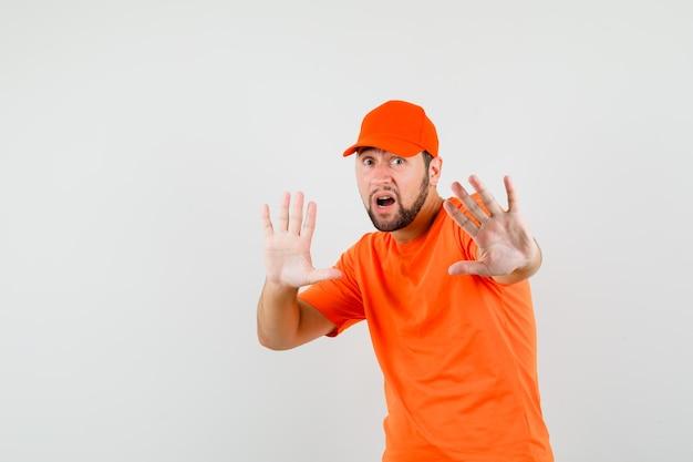 Dostawca w pomarańczowym t-shirt, czapka trzymająca ręce w sposób ochronny i wyglądający na przestraszonego, widok z przodu.