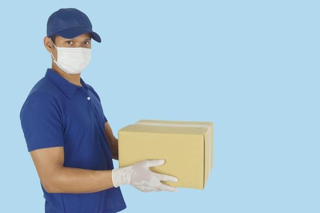 Dostawca w rękawiczkach z maską medyczną i trzymający pudełko w ręku