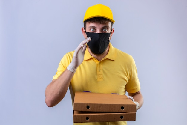 Dostawca w żółtej koszulce polo i czapce w czarnej masce ochronnej trzymający pudełka po pizzy stojący z ręką w pobliżu ust, który mówi sekret na odosobnionym białym tle
