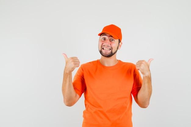 Dostawca wskazujący podwójne kciuki do boku w pomarańczowy t-shirt, czapkę i patrząc wesoło. przedni widok.