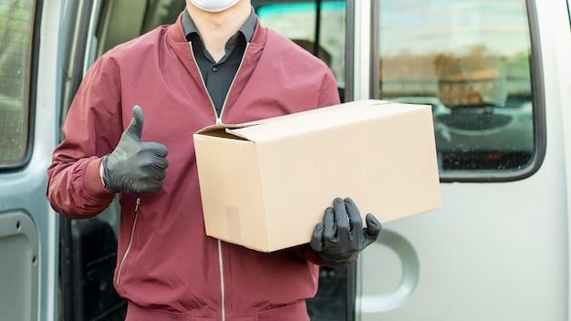 Dostawca wyposażony w rękawice i maskę ochronną. dostawa produktów dzięki symbolowi czasu pandemii.