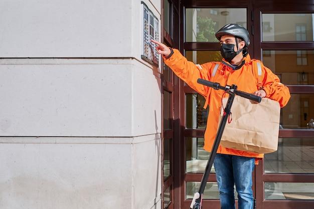 Dostawca z maską na twarz i elektrycznym skuterem dzwoni do drzwi