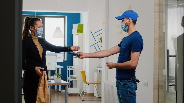 Dostawca z ochronną maseczką medyczną i rękawiczkami przeciwko koronawirusowi przynoszący zamówienie na obiad na wynos w biurze firmy