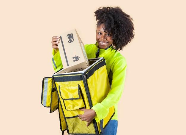 Dostawcza kobieta z plecakiem wyjmująca paczkę, beżowe tło