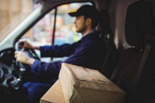 Dostawczy kierowca furgonetki z paczkami na siedzeniu na zewnątrz magazynu