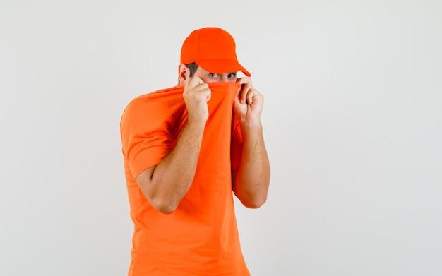 Dostawczy mężczyzna ciągnąc za kołnierz na twarzy w pomarańczowy t-shirt, czapkę i patrząc przestraszony, widok z przodu.