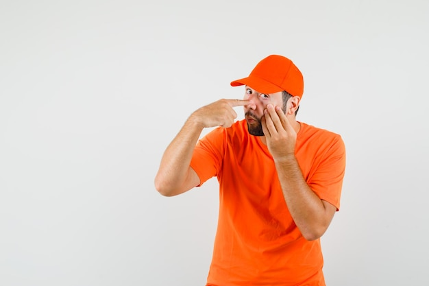 Dostawczy mężczyzna wskazujący na powiekę ściągniętą palcami w pomarańczowym t-shirt, widok z przodu czapki.