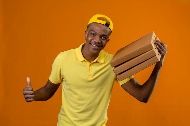 Dostawy afroamerykanin w żółtej koszulce polo i czapce trzymającej pudełka po pizzy pokazujący kciuk do góry z radosną buźką na odizolowanej pomarańczy