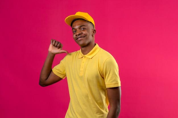 Dostawy afroamerykanin w żółtej koszulce polo i czapce wyglądający pewnie, wskazując kciukiem na siebie dumny zadowolony z siebie stojąc na różowo