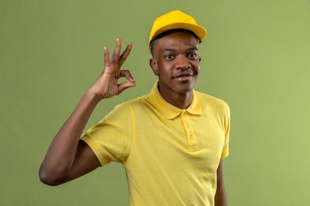 Dostawy afroamerykanin w żółtej koszulce polo i czapce wyglądający radośnie, uśmiechnięty, robi ok znak na zielono
