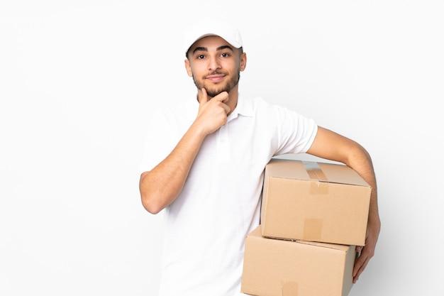 Dostawy arabian mężczyzna na białym tle na niebieskiej ścianie śmiejąc się
