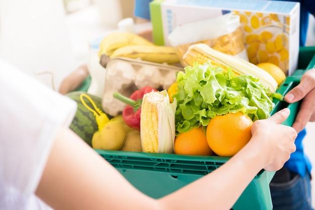Dostawy człowiek dostarczanie artykuły spożywcze do kobiety