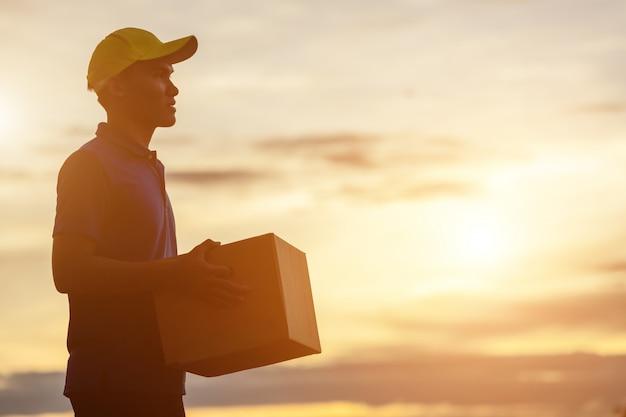 Dostawy człowiek posiadający brązowy paczki lub kartony dostawy do klienta na wsi