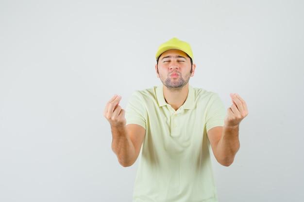 Dostawy człowiek robi gest pieniędzy, wydymane usta w żółtym jednolitym widoku z przodu.