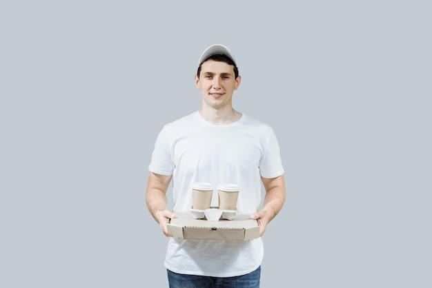 Dostawy mężczyzna trzyma pudełko po pizzy i kawę