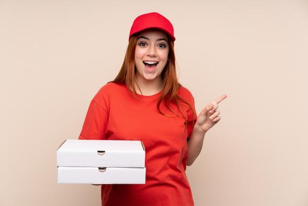 Dostawy pizzy nastolatka dziewczyna trzyma palec wskazujący palec na bok