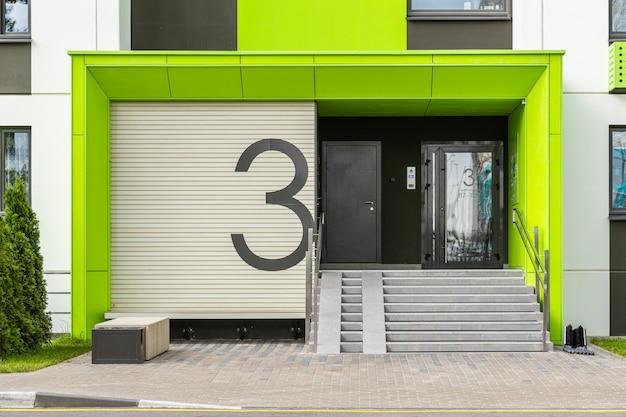 Dostęp do budynku numer trzy ze szklanymi drzwiami, rampą wjazdową i domofonem