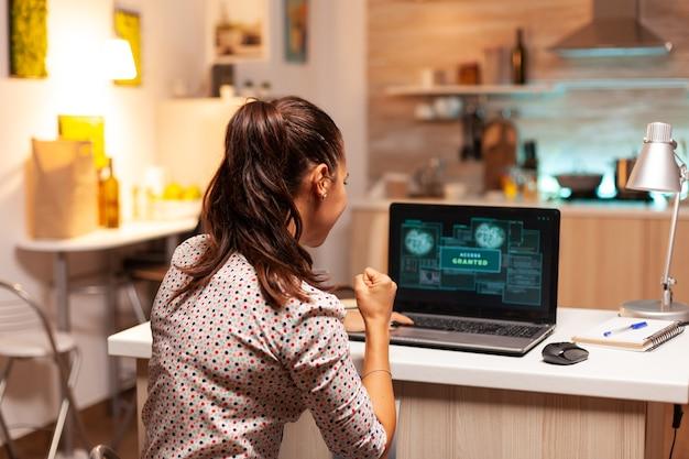 Dostęp przyznany kobiecie hakerowi po cyberataku. programista piszący niebezpieczne złośliwe oprogramowanie do cyberataków przy użyciu wydajnego laptopa o północy.
