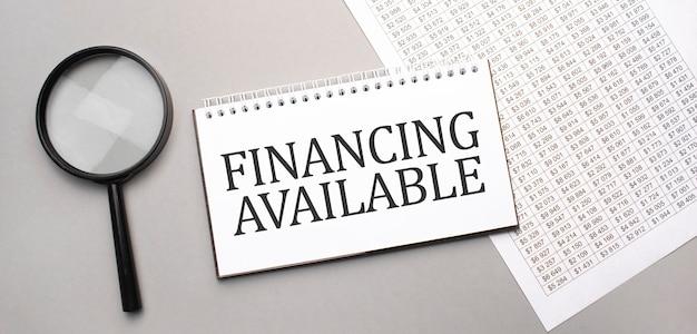 Dostępne finansowanie zarejestruj się w notatniku na białym papierze i szkło powiększające na szaro