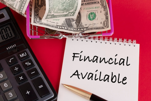 Dostępne finansowe, tekst napisany w białym notatniku na czerwonym tle.