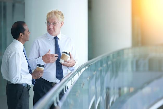 Doświadcz przedsiębiorcę stojącego na balkonie biurowca pijącego kawę