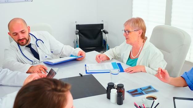 Doświadczeni dojrzali lekarze wyjaśniający młodym lekarzom diagnozę pacjenta podczas konferencji. ekspert kliniczny terapeuta rozmawiający z kolegami o chorobie, specjalista od medycyny.