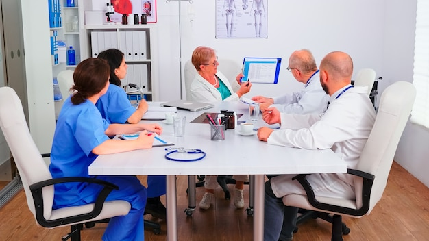 Doświadczeni lekarze w szpitalnej sali konferencyjnej współpracujący podczas seminarium zdrowotnego, starszy lekarz wskazujący na schowek. ekspert terapeuta rozmawiający z kolegami o chorobie, specjalista od medycyny