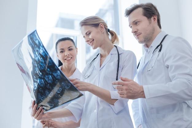 Doświadczeni, radośni, wykwalifikowani onkolodzy pracujący w laboratorium medycznym i prowadzący dyskusję, trzymając wynik tomografii komputerowej