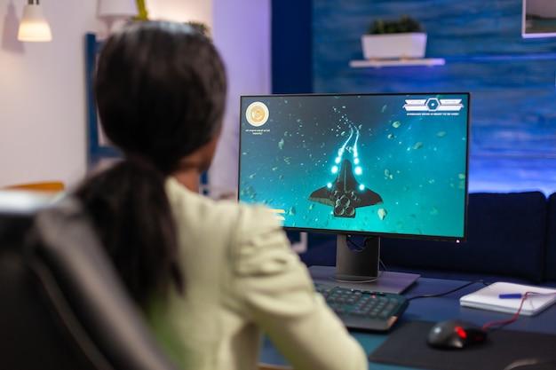 Doświadczona kobieta grająca w kosmiczną strzelankę na potężnym komputerze. konkurencyjna kobieta gracza cybernetycznego podczas turnieju gier wideo używa profesjonalnego joysticka.