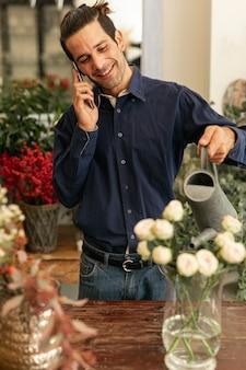 Doświadczona kwiaciarnia rozmawia przez telefon