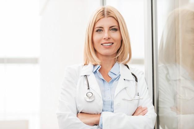 Doświadczona lekarka. pewna siebie lekarka w białym mundurze, patrząca w kamerę i uśmiechnięta, opierając się o szklaną ścianę