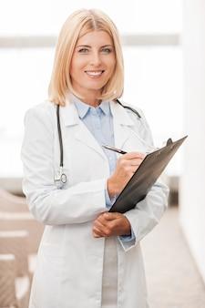 Doświadczona lekarka. pewna siebie lekarka w białym mundurze pisze coś w schowku i uśmiecha się stojąc w korytarzu kliniki