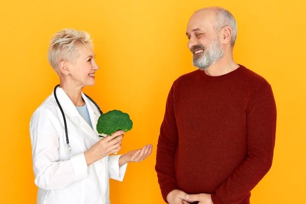 Doświadczona lekarka w średnim wieku trzymająca brokuły w dłoniach, opowiadająca o korzyściach zdrowej żywności ekologicznej dla brodatego starszego mężczyzny