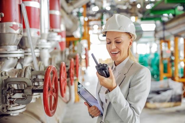 Doświadczona pracowita przełożona w średnim wieku w kasku w garniturze, trzymająca tablet w rękach i rozmawiająca przez walkie talkie z pracownikiem stojąc w ciepłowni.