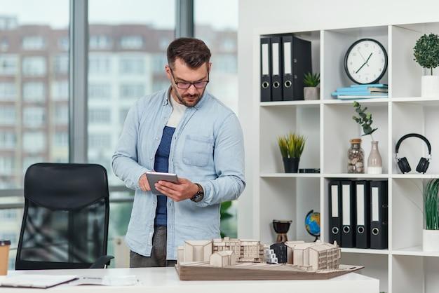 Doświadczony architekt płci męskiej w biurze sprawdza projekt kompleksu mieszkalnego i wykonuje obliczenia za pomocą tabletu.