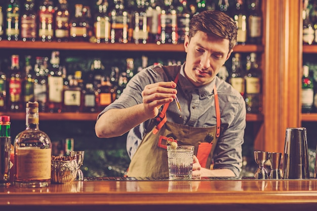 Doświadczony barman robi koktajl w klubie nocnym lub barze.
