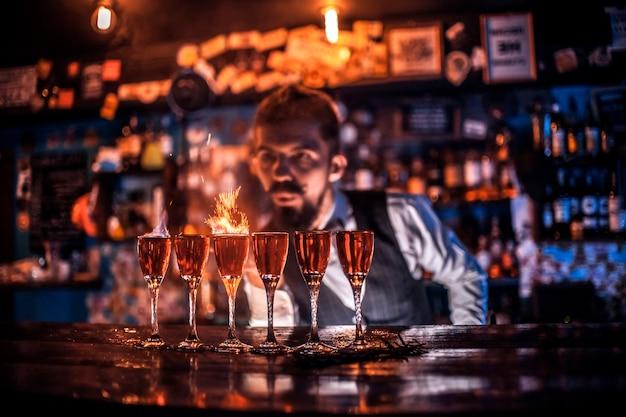 Doświadczony barman wlewający świeży napój alkoholowy do szklanek w barze