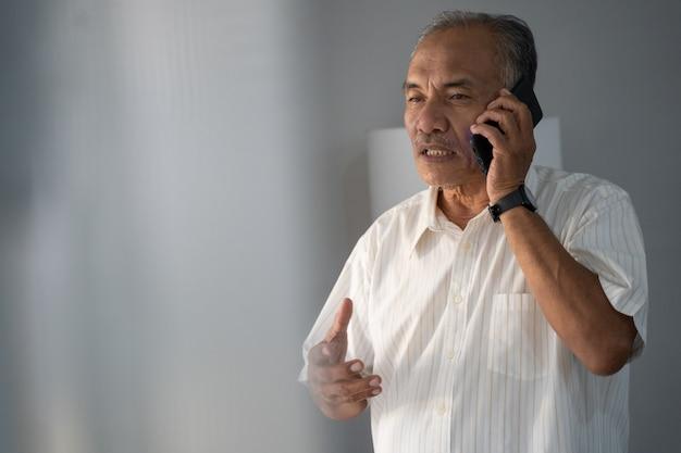 Doświadczony biznesmen rozmawia przez telefon za pomocą smartfona do dwukierunkowej komunikacji