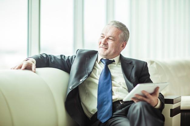 Doświadczony biznesmen z cyfrowym tabletem, siedząc na kanapie w prywatnym biurze.