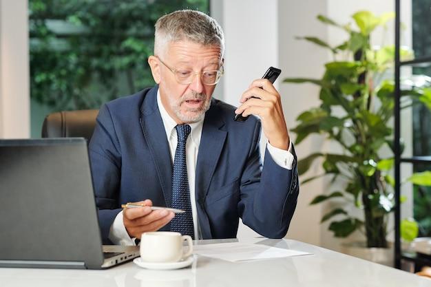 Doświadczony dojrzały biznesmen nagrywa wiadomość głosową dla swojego asystenta podczas czytania dokumentu biznesowego lub umowy