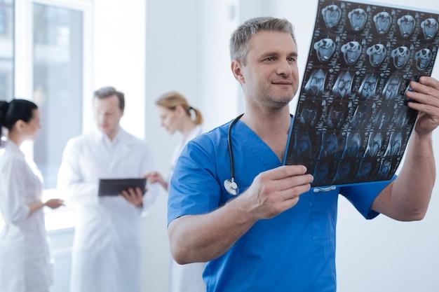 Doświadczony dojrzały przystojny onkolog pracujący w laboratorium medycznym i oglądający tomografię komputerową, podczas gdy jego koledzy używają gadżetu z tyłu