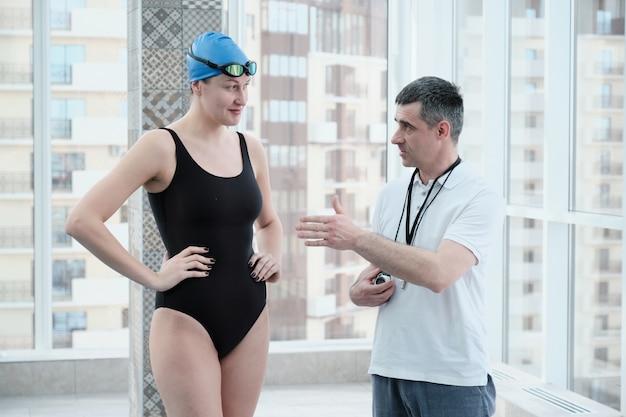 Doświadczony dojrzały trener wskazujący ręką podczas omawiania planu treningu pływackiego z pływaczką