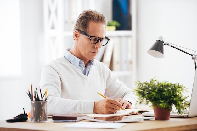 Doświadczony ekspert w pracy. pewny siebie dojrzały mężczyzna piszący coś w swoim zeszycie, siedząc w swoim miejscu pracy