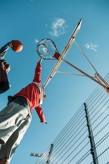 Doświadczony gracz. ładny wysportowany mężczyzna podskakując dotykając kosza do koszykówki