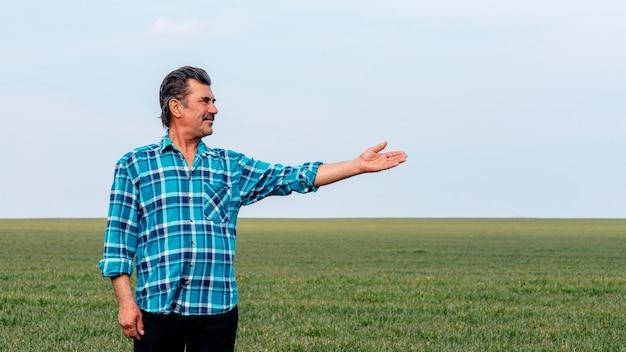Doświadczony i pewny siebie rolnik stoi na swoim polu z wyciągniętą ręką.
