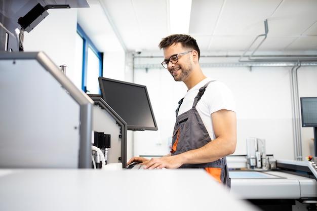 Doświadczony inżynier mechatronik sprawdzający zautomatyzowany system robotyki w fabrycznym pomieszczeniu testowym.