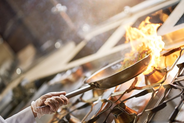 Doświadczony kucharz trzymający patelnię w płomieniach nad piecem